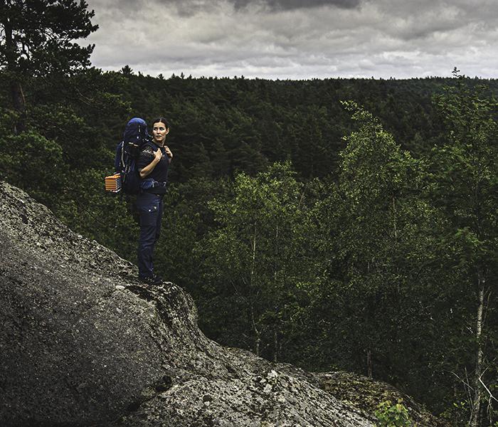 kvinde med rygsæk på klippe